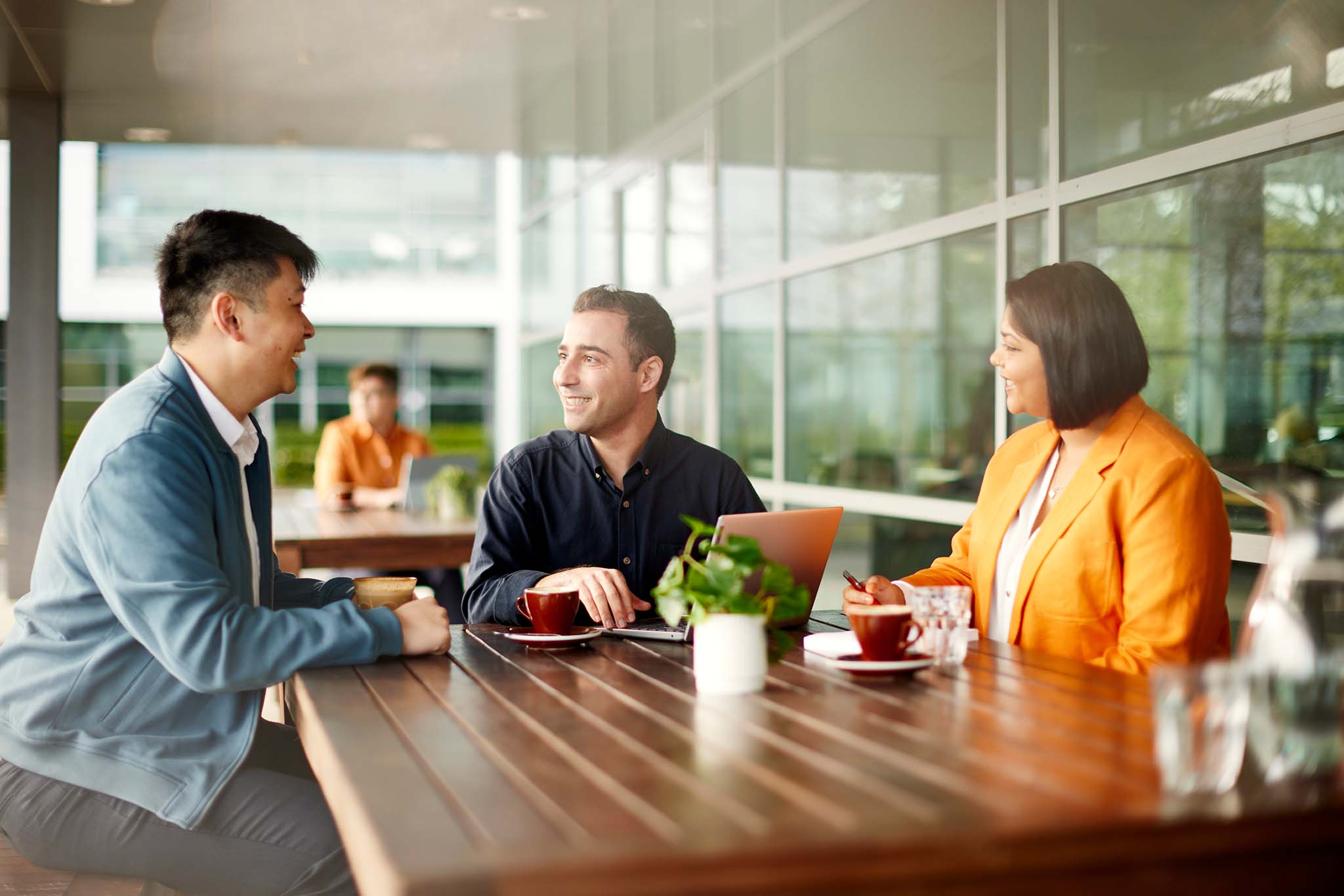 Three people enjoy a business meeting at a cafe